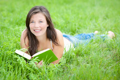 Outdoor portrait of a cute reading teen Stock Image