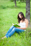 Outdoor portrait of a cute reading teen Stock Photos