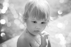 Outdoor portrait of cute thinking blond baby girl Royalty Free Stock Photos