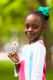 Outdoor portrait of a cute young black girl holding a dandelion. Flower - African people Royalty Free Stock Photography