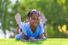 Outdoor portrait of a cute young black girl  lying down on the g Stock Image
