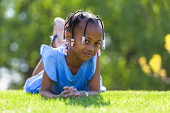 Outdoor portrait of a cute young black girl  lying down on the g Stock Photos