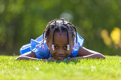 Outdoor portrait of a cute young black girl  lying down on the g Royalty Free Stock Photo