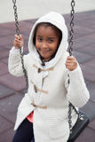 Outdoor portrait of a cute young black girl playing with a swing Royalty Free Stock Image