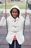 Outdoor portrait of a cute young black girl playing with a swing Royalty Free Stock Images