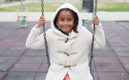 Outdoor portrait of a cute young black girl playing with a swing Stock Photo