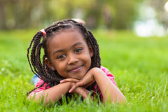 Outdoor portrait of a cute young black girl smiling - African pe. Outdoor portrait of a cute young black girl  lying down on the grass and smiling - African Royalty Free Stock Image