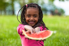 Outdoor portrait of a cute young black little girl eating waterm royalty free stock image