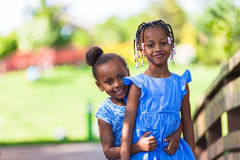 Outdoor  portrait of a cute young black sisters - African people Royalty Free Stock Images