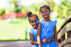 Outdoor portrait of a cute young black sisters - African people royalty free stock photo