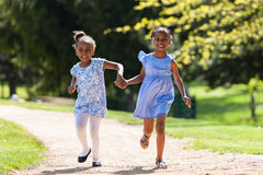 Outdoor  portrait of a cute young black sisters running - Africa Stock Photo