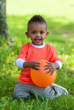 Outdoor portrait of a cute young  little black boy playing with Royalty Free Stock Photography