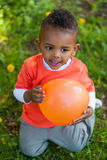 Outdoor portrait of a cute young  little black boy playing with Stock Photos
