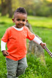 Outdoor portrait of a cute young  little black boy playing outsi Stock Photos