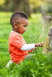 Outdoor portrait of a cute young  little black boy playing outsi Royalty Free Stock Images