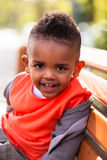 Outdoor portrait of a cute young  little black boy seated on a b Stock Photo