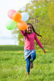 Outdoor portrait of a cute young  little black girl playing with. Balloons - African people Royalty Free Stock Photo