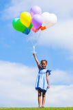 Outdoor portrait of a cute young  little black girl playing with. Balloons - African people Stock Photo