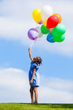 Outdoor portrait of a cute young  little black girl playing with. Balloons - African people Stock Image