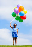 Outdoor portrait of a cute young  little black girl playing with. Balloons - African people Royalty Free Stock Photography