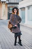 Outdoor portrait of elegant young lady with brown backpack wearing coat and hat. Attractive girl with curly hair stock photo