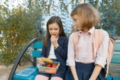 Outdoor portrait of elementary school students with lunch boxes, healthy school breakfast. Children eat, talk, laugh stock photo