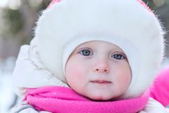 Outdoor portrait face of a little girl in a cap close-up in on t. He background snow winter royalty free stock images