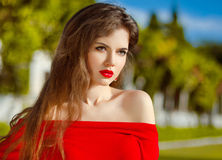 Outdoor portrait of fashion brunette model in red dress. Romanti Royalty Free Stock Image