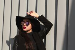 Outdoor portrait of fashionable model posing in black coat and b. Outdoor portrait of fashionable woman posing in black coat and broad brimmed hat. Female Stock Photography