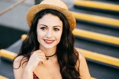 Outdoor portrait of fashionable woman with dark thick hair having make-up and painted red lips wearing summer straw hat and neckla royalty free stock image