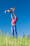 Outdoor portrait of a father who throws daughter in the air against the sky Royalty Free Stock Image