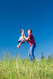 Outdoor portrait of a father who throws daughter in her arms Royalty Free Stock Photos