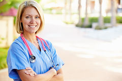 Outdoor Portrait Of Female Nurse. Crossing Her Arms Smiling At Camera