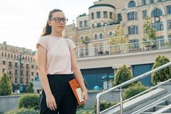 Outdoor portrait of female student 16, 17 years old. Girl in glasses, with backpack, textbooks. City background.  royalty free stock photography