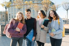 Outdoor portrait of a female teacher and group of teenage students, golden hour stock image
