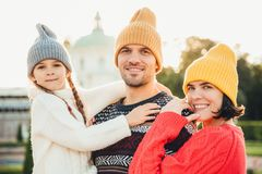 Outdoor portrait of friendly family stand close to each other, have broad smiles. Pretty woman in yellow trendy hat and red sweate royalty free stock photography