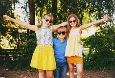 Outdoor portrait of 3 funny kids playing together. In summer park. Happy childhood royalty free stock photos