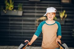 Outdoor fashion portrait of cute preteen girl. Outdoor portrait of funny preteen girl wearing multi raglan top and white cap Royalty Free Stock Image