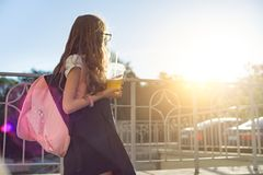 Outdoor portrait of girl elementary school student wearing glasses, school uniform, with backpack drinking natural juice from royalty free stock photography