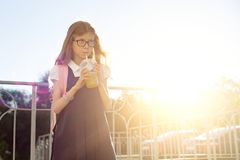 Outdoor portrait of girl elementary school student wearing glasses, school uniform, with backpack drinking natural juice from royalty free stock images