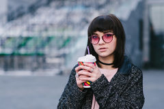 Outdoor portrait of a girl in pink glasses holding a colorful cup of hot drink against Royalty Free Stock Photography