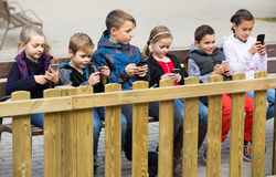 Outdoor portrait of girls and boys playing with phones stock images