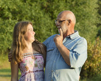 Outdoor portrait of  grandfather with granddaughter. Stock Photos