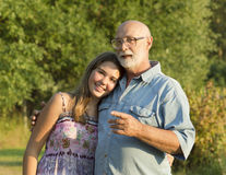 Outdoor portrait of  grandfather with granddaughter. Royalty Free Stock Images