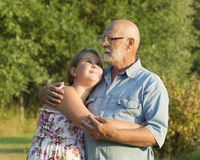 Outdoor portrait of  grandfather with granddaughter. Royalty Free Stock Photography