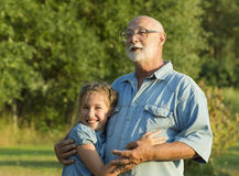 Outdoor portrait of  grandfather with granddaughter. Stock Images