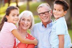 Outdoor Portrait Of Grandparents With Grandchildren In Park Stock Photos
