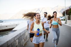 Outdoor portrait of group of friends running and jogging in nature royalty free stock photos