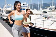 Outdoor portrait of group of happy fit women running stock images