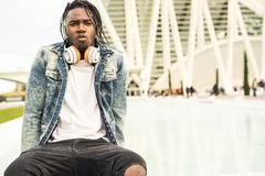 Outdoor portrait of a handsome and attractive young African man with music headphones on the street. Concept of technology stock images